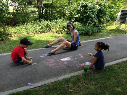 Kids doing chalk art with an Eliot member