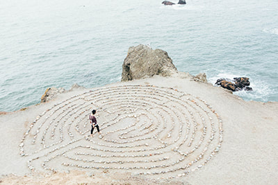 Labyrinth in the sand with stones, by the sea